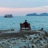 Uomo solo che si siede su un banco che esamina il mare Fotografie Stock