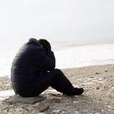 Uomo solo che si siede sulla sabbia Fotografia Stock Libera da Diritti