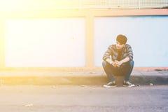 Uomo solo che si siede sulla via Immagine Stock