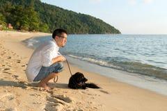 Uomo con il cane alla spiaggia Immagine Stock