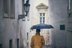 Uomo solo con l'ombrello in pioggia fotografia stock libera da diritti