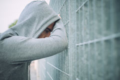 Uomo solo e depresso che pende contro un recinto Fotografie Stock