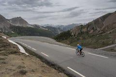 Uomo solo sulla bicicletta quasi alla cima del izoard del ` del passo d nell'Alta Provenza francese Immagini Stock