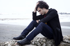 Uomo solo triste che si siede davanti all'oceano con le onde nell'inverno Fotografia Stock Libera da Diritti