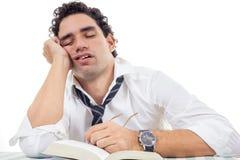 Uomo sonnolento con i vetri in camicia bianca ed in legame che si siedono con il libro Immagini Stock