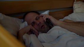 Uomo sonnolento con il telefono video d archivio