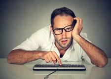 Uomo sonnolento del lavoratore che lavora al computer Immagine Stock