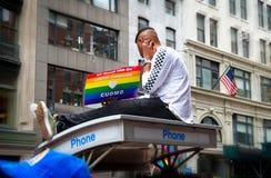 Uomo sopra la cabina telefonica che tiene un segno a New York 2018 Pride Parade Immagini Stock