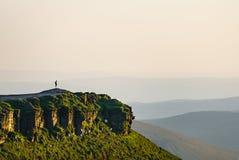 Uomo sopra la valle di sguardi al tramonto Fotografia Stock