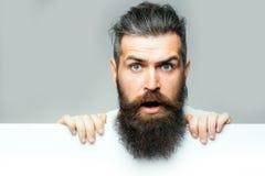Uomo sorpreso barbuto con carta Fotografia Stock