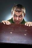 Uomo sorpreso che fissa alla cassa aperta Immagine Stock