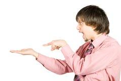 Uomo sorpreso che mostra qualcosa sulla sua mano Immagine Stock