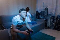 Uomo sorpreso e furioso appassionato circa un gioco che si siede al hom Fotografia Stock