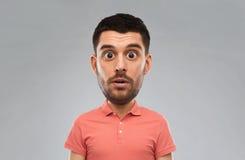 Uomo sorpreso in maglietta di polo sopra fondo grigio Immagine Stock