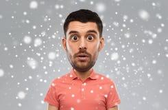 Uomo sorpreso in maglietta di polo sopra il fondo della neve Immagini Stock