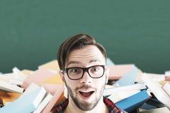 Uomo sorpreso in vetri e libri nella classe Immagine Stock