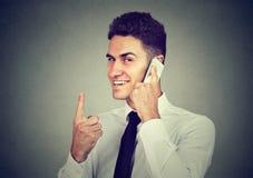 Uomo sorridente adulto che parla sul dito della tenuta del telefono su immagini stock