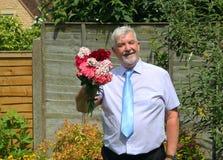 Uomo sorridente astuto che dà mazzo di fiori Immagine Stock Libera da Diritti