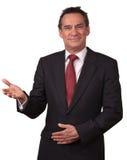 Uomo sorridente attraente in vestito che Gesturing benvenuto Immagini Stock Libere da Diritti
