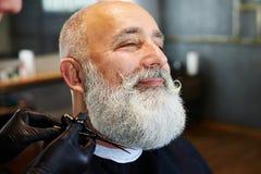 Uomo sorridente barbuto nel negozio di barbiere Immagine Stock Libera da Diritti