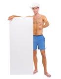 Uomo sorridente in cappello che mostra tabellone per le affissioni in bianco Fotografie Stock