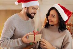 Uomo sorridente in cappello di Santa che dà il regalo di Natale alla moglie Fotografia Stock