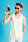 Uomo sorridente in cappello ed occhiali da sole che tengono bottiglia di soda fotografie stock
