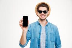 Uomo sorridente in cappello ed occhiali da sole che tengono lo smartphone dello schermo in bianco immagine stock libera da diritti