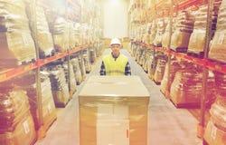 Uomo sorridente in carico di caricamento dell'elmetto protettivo al magazzino Immagine Stock