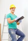 Uomo sorridente in casco protettivo con la lavagna per appunti fotografia stock libera da diritti