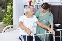 Uomo sorridente che è aiutato dalla struttura di In Using Zimmer dell'infermiere immagini stock