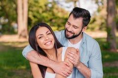 Uomo sorridente che abbraccia moglie felice all'aperto fotografie stock libere da diritti