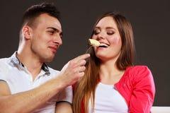 Uomo sorridente che alimenta donna felice con la banana Fotografie Stock Libere da Diritti