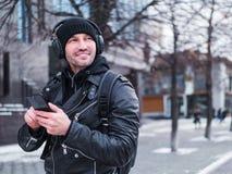 Uomo sorridente che ascolta la musica tramite cuffie, collegate al telefono da bluetooth Fotografie Stock Libere da Diritti