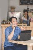 Uomo sorridente che chiama dal telefono nel caffè Immagine Stock
