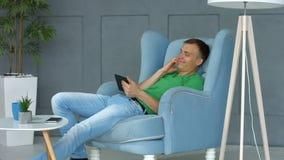 Uomo sorridente che controlla applicazione di Internet sulla compressa archivi video