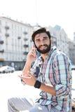 Uomo sorridente che distoglie lo sguardo mentre utilizzando telefono cellulare nella città Fotografia Stock