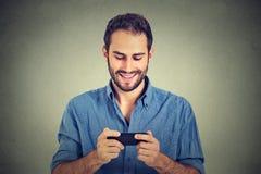 Uomo sorridente che esamina il suo Smart Phone mentre invio di messaggi di testo o che guarda video Fotografie Stock Libere da Diritti