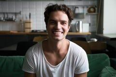 Uomo sorridente che esamina macchina fotografica che si siede sul sofà della cucina, ritratto Fotografie Stock Libere da Diritti
