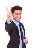 Uomo sorridente che fa il segno di vittoria Immagine Stock Libera da Diritti