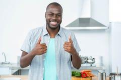 Uomo sorridente che gesturing i pollici su in cucina Fotografie Stock Libere da Diritti