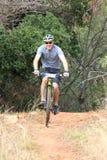 Uomo sorridente che gode all'aperto del giro alla corsa del mountain bike Fotografie Stock