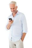 Uomo sorridente che invia un messaggio di testo Fotografie Stock Libere da Diritti