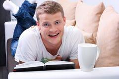 Uomo sorridente che legge un libro e che si distende sul sofà Fotografia Stock