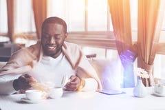 Uomo sorridente che mette zucchero nel tè fotografia stock libera da diritti