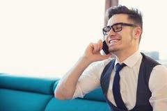 Uomo sorridente che parla sul telefono a casa fotografia stock