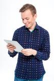 Uomo sorridente che per mezzo del computer della compressa Immagini Stock