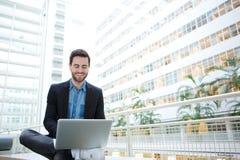 Uomo sorridente che per mezzo del computer portatile Fotografia Stock Libera da Diritti