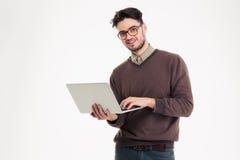 Uomo sorridente che per mezzo del computer portatile Fotografia Stock