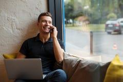 Uomo sorridente che per mezzo del suo computer portatile e telefonando sul sofà alla finestra Immagine Stock Libera da Diritti